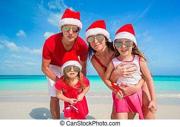Portrait of happy family in Santa hats on the beach - Happy...