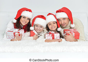 family in Santa hats with gifts