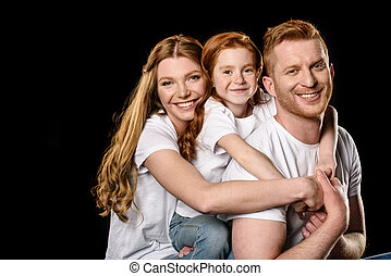 portrait of happy family in white t-shirts hugging each other isolated on black