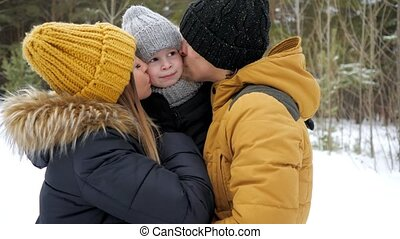 Mom and dad are cuddling and kissing their little son in winter park.