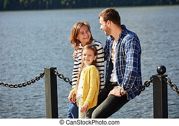 Happy Family looking at camera while posing on pier at quiet lake