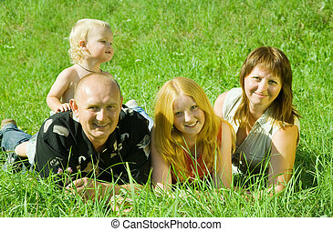 family of four laying on grass
