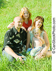 family of four sitting on grass