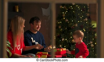 Portrait of happy family opening a Christmas present gift...