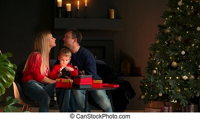 Portrait of happy family opening a Christmas present gift box in the evening. Concept of holidays, surprise, happy family, e-commerce, online shopping.