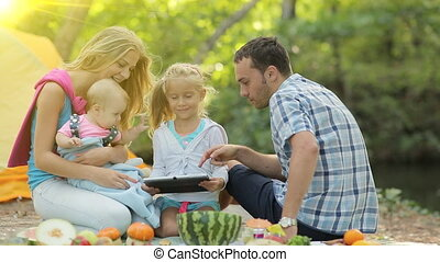 Portrait of happy family sitting on a picnic with the tablet