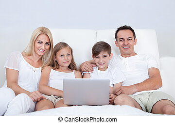 Portrait Of Happy Family Sitting On Bed