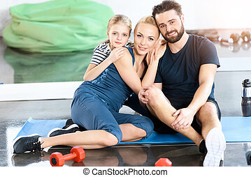 Portrait of happy family sitting on mat at gym