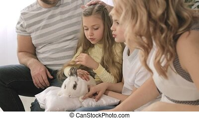Portrait of happy family that is stroking a rabbit while sitting on the sofa