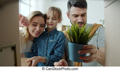 Portrait of happy family with child unpacking things during relocation looking at memorable belongings talking and smiling then looking at camera and closing box