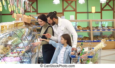 Beautiful parents and their daughter are choosing sweets in supermarket.