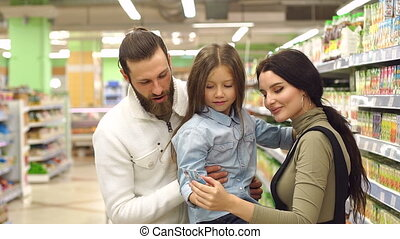 Portrait of happy family with cute little girl choosing juice in grocery store.