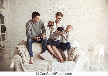 portrait of happy family with pet dog on sofa in living room