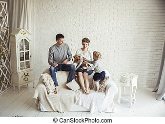 portrait of happy family with pet dog on sofa in living room...