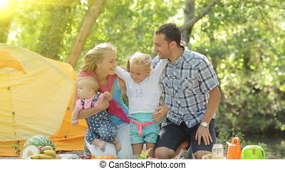 Portrait of happy family with two young children in nature