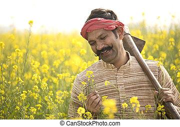 Portrait of happy farmer holding hoe in rapeseed field
