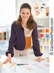 Portrait of happy fashion designer in office