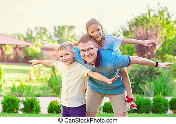 Portrait of happy father and two cute children playing at courtyard