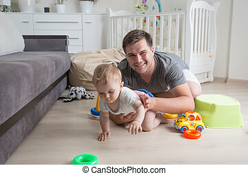 Portrait of happy father crawling with his baby boy on floor at living room