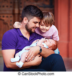 portrait of happy father with newborn baby and son