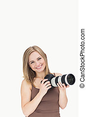 Portrait of happy female with photographic camera over white...