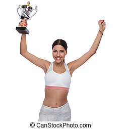 portrait of happy fitness woman holding winning sports cup