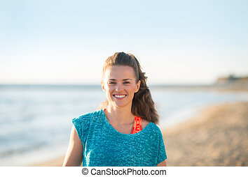 Portrait of happy fitness young woman on beach in evening