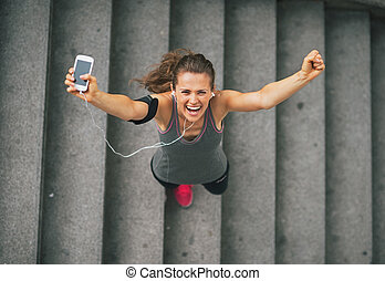 Portrait of happy fitness young woman with cell phone...