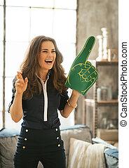 Portrait of happy football fan woman watching tv in loft apartme