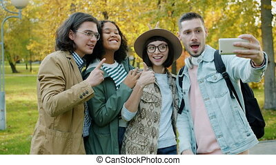 Portrait of happy friends tourists taking selfie in park showing thumbs-up