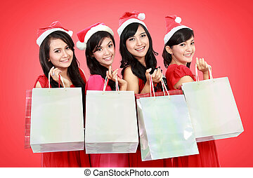 Portrait of happy funny people with christmas santa hat holding gift boxes