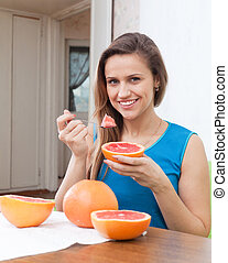 girl eating grapefruit at home
