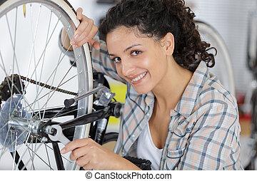 portrait of happy girl fixing wheels in workshop