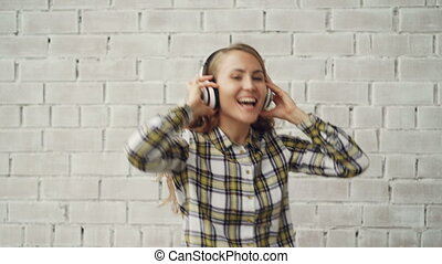 Portrait of happy girl in stylish clothing dancing, singing and listening to music in wireless headphones. Millennials, modern electronics and young people concept.