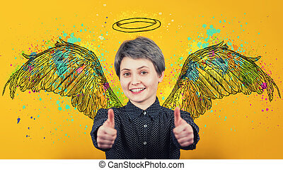 Portrait of happy girl keeps thumbs up over yellow background, smiling broadly imagining herself an angel with fluffy wings behind back and a halo above head.