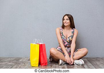 Portrait of happy girl sitting on floor with legs crossed