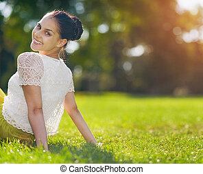 Portrait of happy girl sitting on meadow