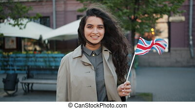 Portrait of happy girl standing outdoors with British flag...