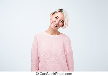 Portrait of happy girl with dyed hair in pink sweater smiling looking at camera.