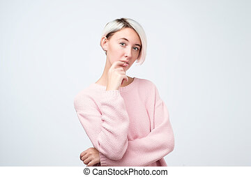 Portrait of happy girl with dyed hair in pink sweater thinking looking at camera.