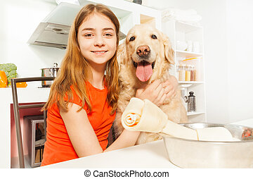 Portrait of happy girl with her pet in the kitchen