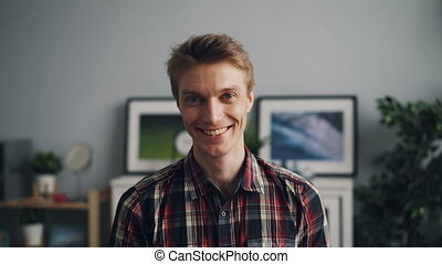 Portrait of happy good-looking guy in trendy checkered shirt...