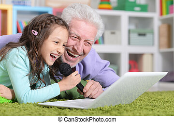 happy grandfather and child singing karaoke