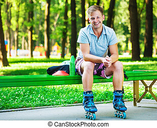 Portrait of happy handsome male roller sitting on bench in the park.