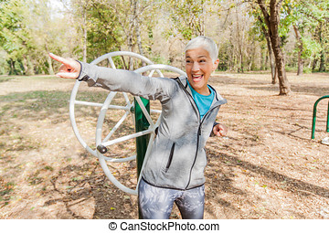 Happy Healthy Senior Woman Workout At Outdoor Gym In Nature