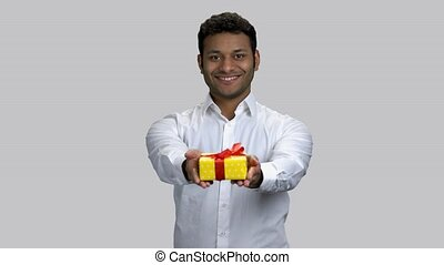 Portrait of happy hindu man giving gift box to you. Cheerful brown-skinned guy with present. Grey isolated background.