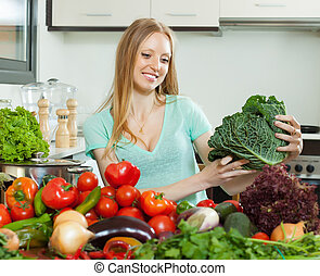 housewife with raw cabbage and other vegetables