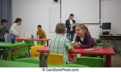 Portrait of happy kids during break in classroom at ...