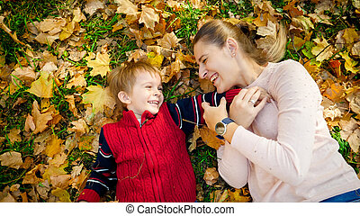 Portrait of happy laughing boy with mother lying on autumn ...