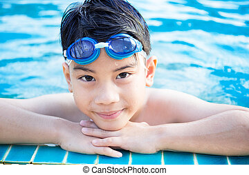 Portrait of happy little boy playing in the pool